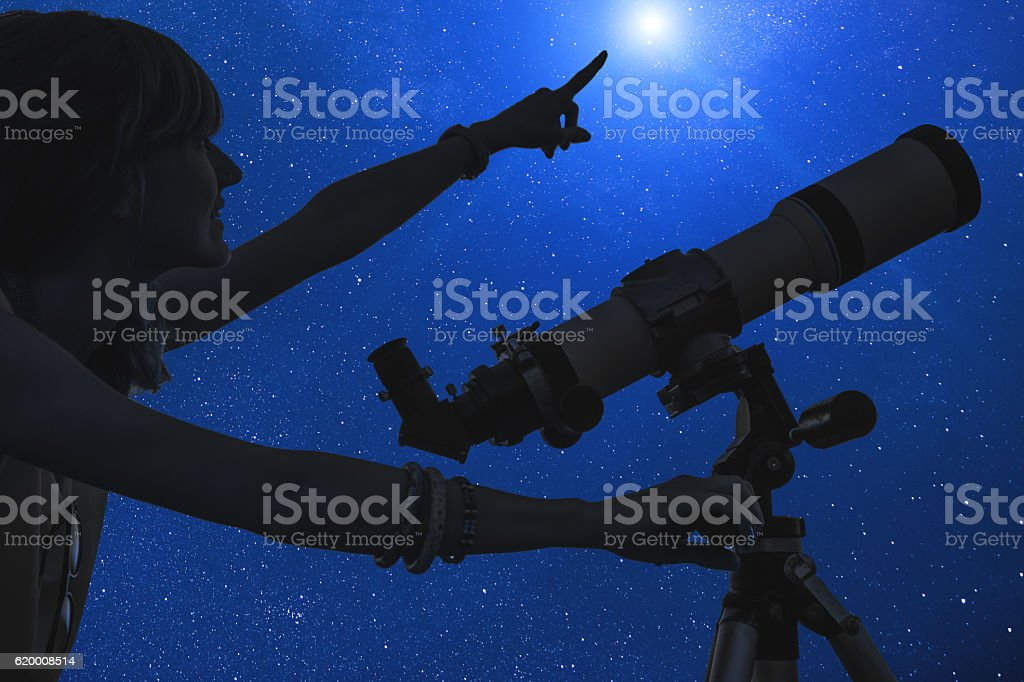 Girl looking at the stars with telescope beside her. Milky Way stars...