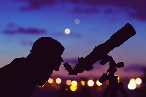 fille regardant les étoiles avec un télescope à côté de son. - astronomie photos et images de collection