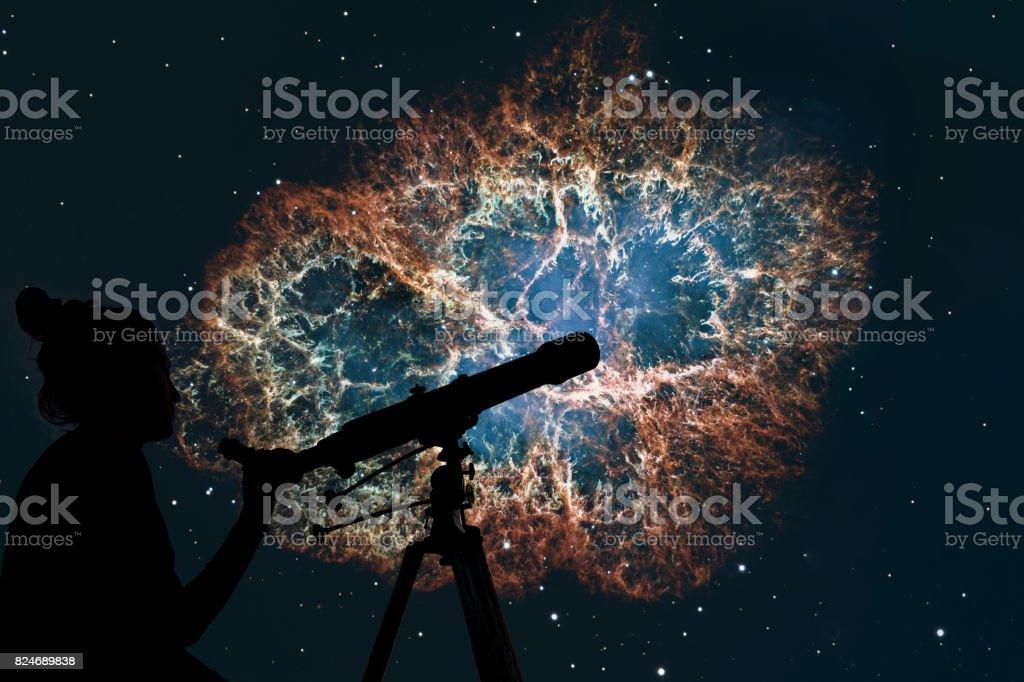 Girl looking at the stars with telescope. Crab Nebula in constellation Taurus. Supernova Core pulsar neutron star. stock photo