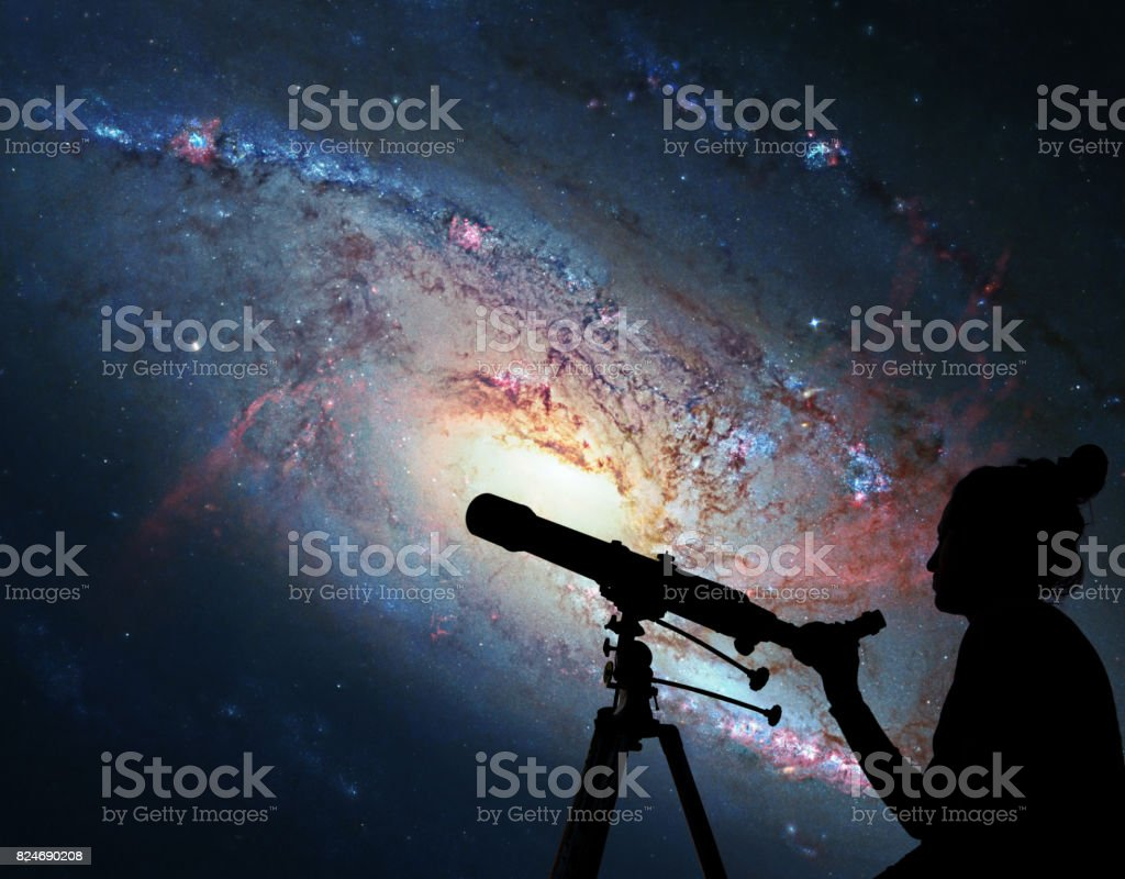 Girl looking at the stars with telescope. Spiral Galaxy M106, in the constellation Canes Venatici. stock photo