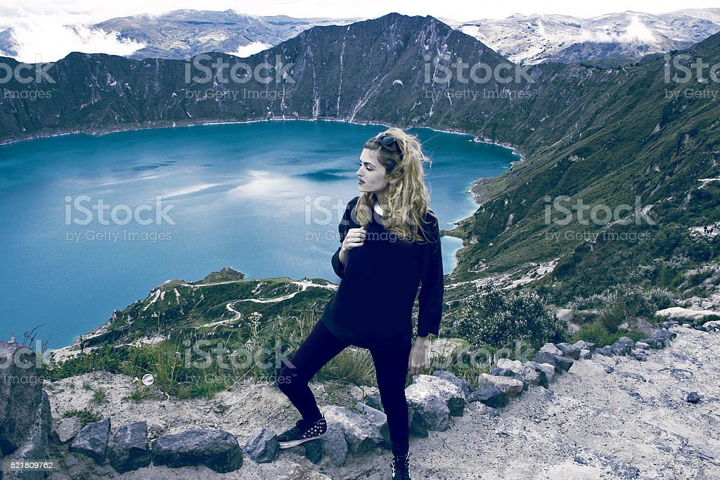 girl looking at view of lake of Quilotoa caldera, Ecuador stock photo
