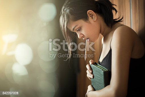 istock Girl looking down and thinking while holding book and pencil. 542207028
