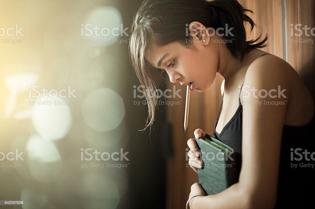 Girl looking down and thinking while holding book and pencil. stok fotoğrafı