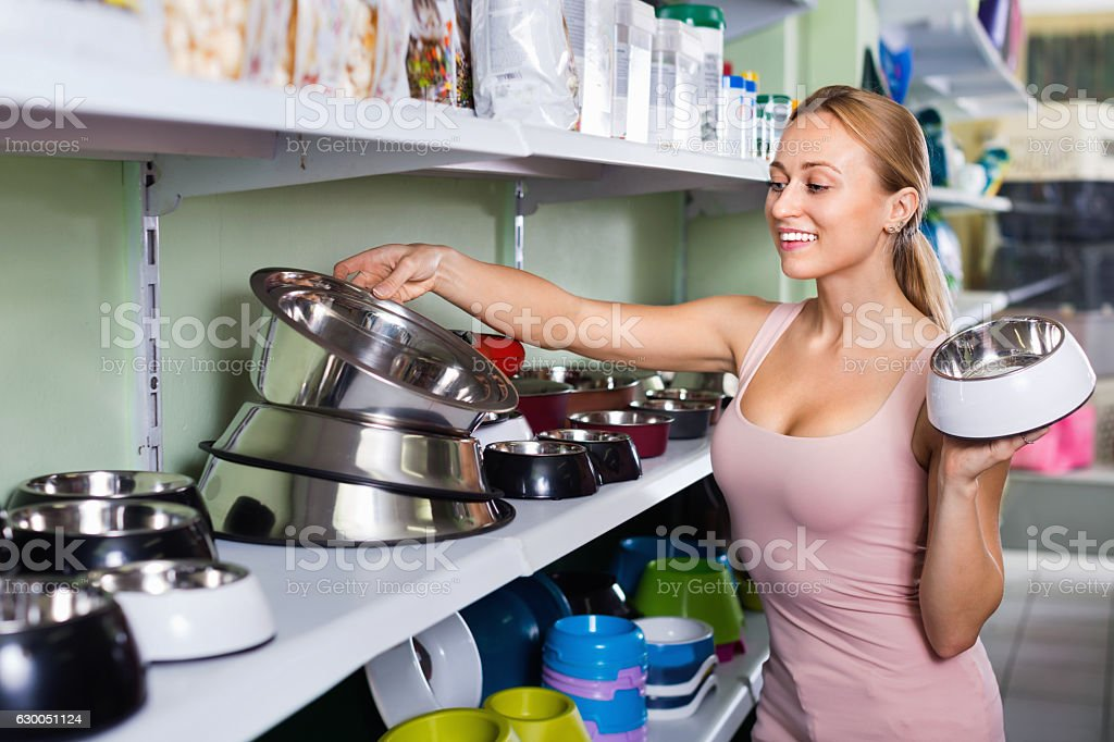 Girl looking for pet bowls in pet shop stock photo
