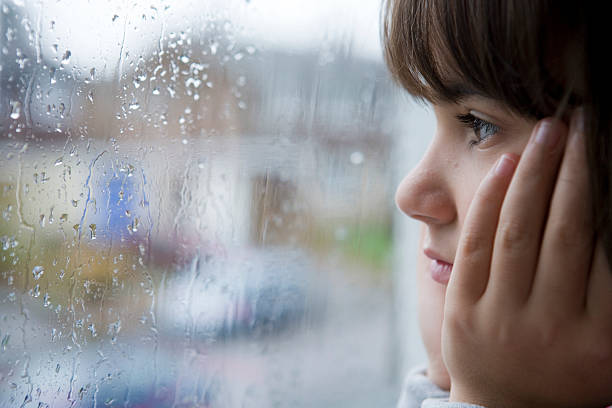 Girl looking out a rain splattered window stock photo