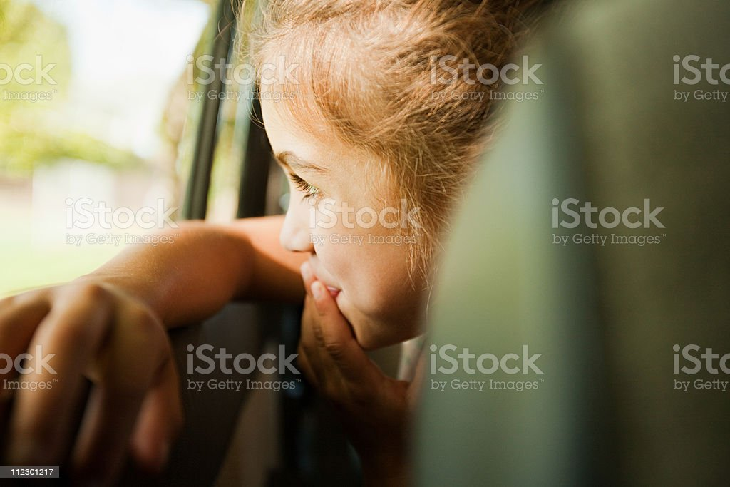 Girl looking out car window stock photo
