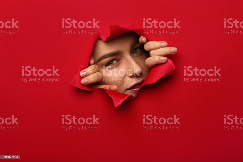 Young woman tearing red paper and looking out of it at camera.