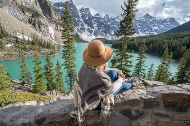 Girl looking out spectacular mountain lake landscape Young woman wrapped in blanket on rock above mountain lake in Springtime. People success in nature concept moraine lake stock pictures, royalty-free photos & images