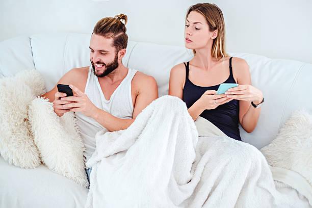 Girl looking over her boyfriend shoulder at his phone - foto de stock