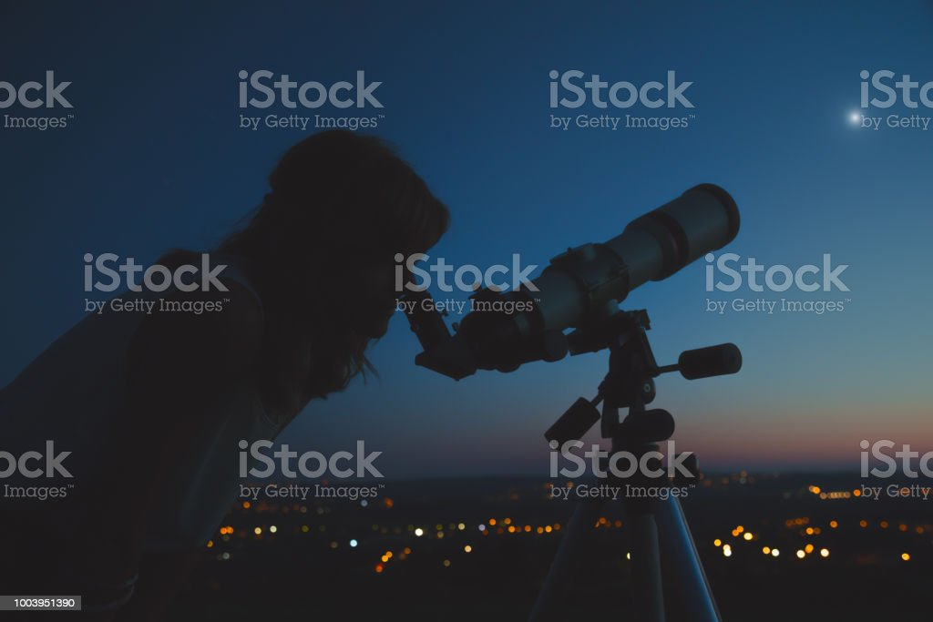 Girl looking through a telescope at the stars.