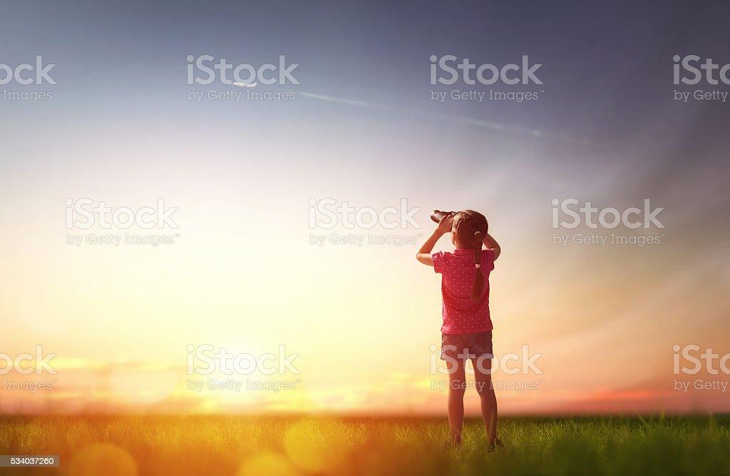 girl looking through binoculars stock photo