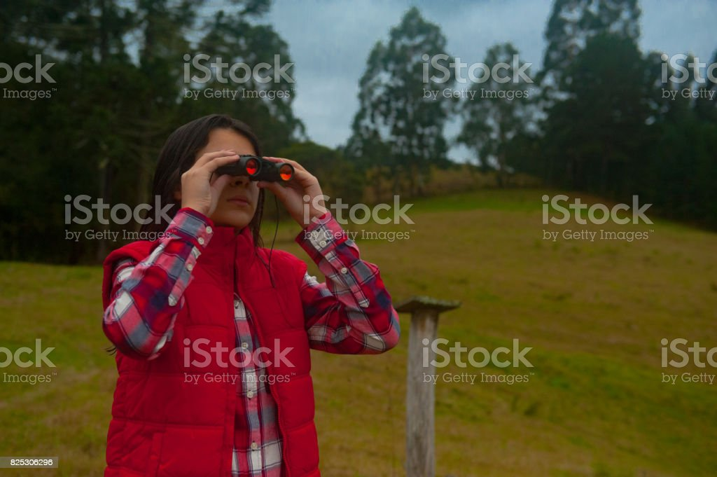 Girl looking through binoculars to observe the birds of nature stock photo