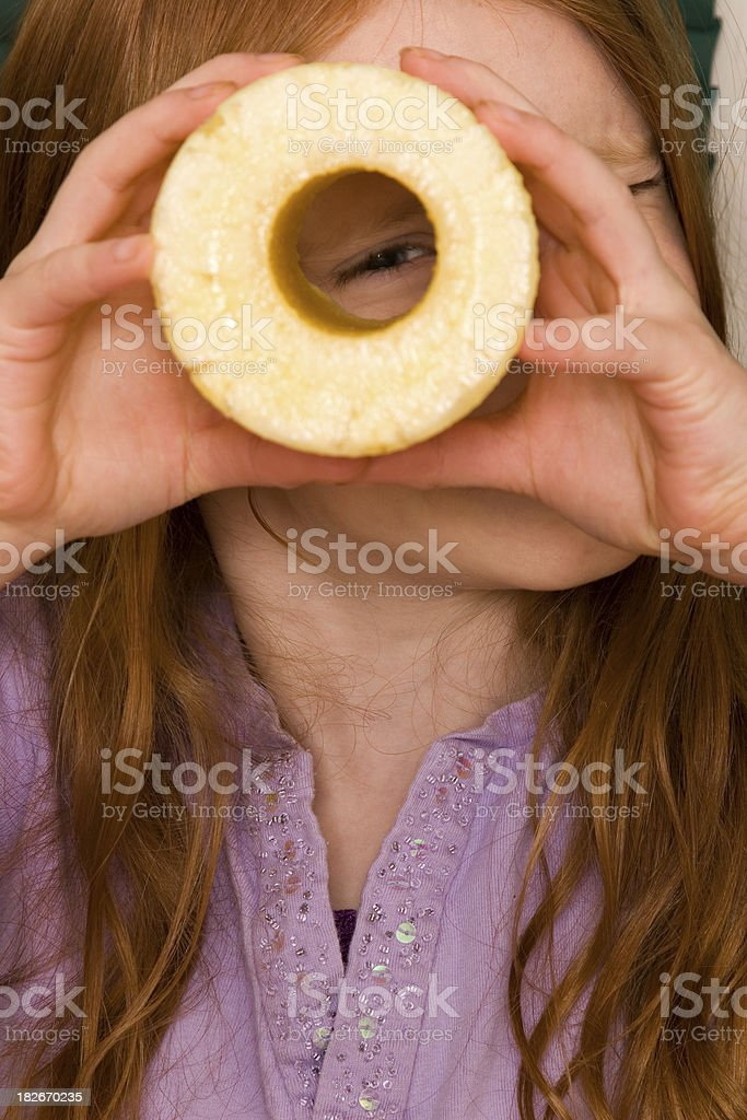 Girl looking through cored pineapple stock photo