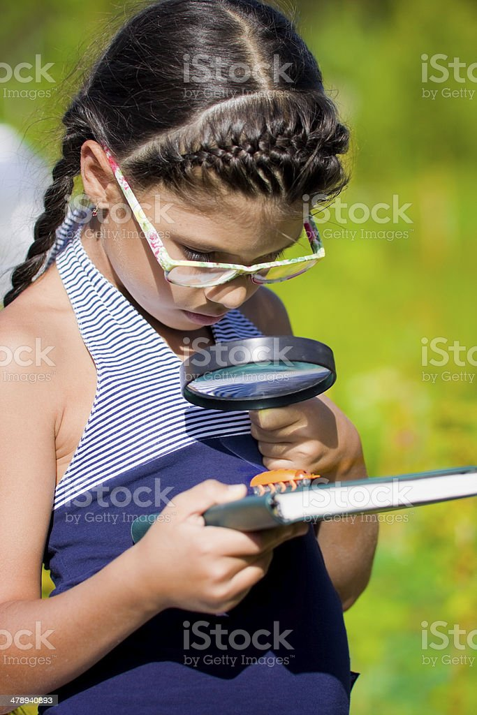 girl looking through magnifying glass on beetle royalty-free stock photo