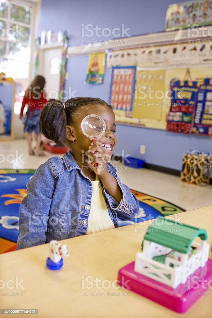 Girl (4-5) looking through magnifying glass royalty-free stock photo