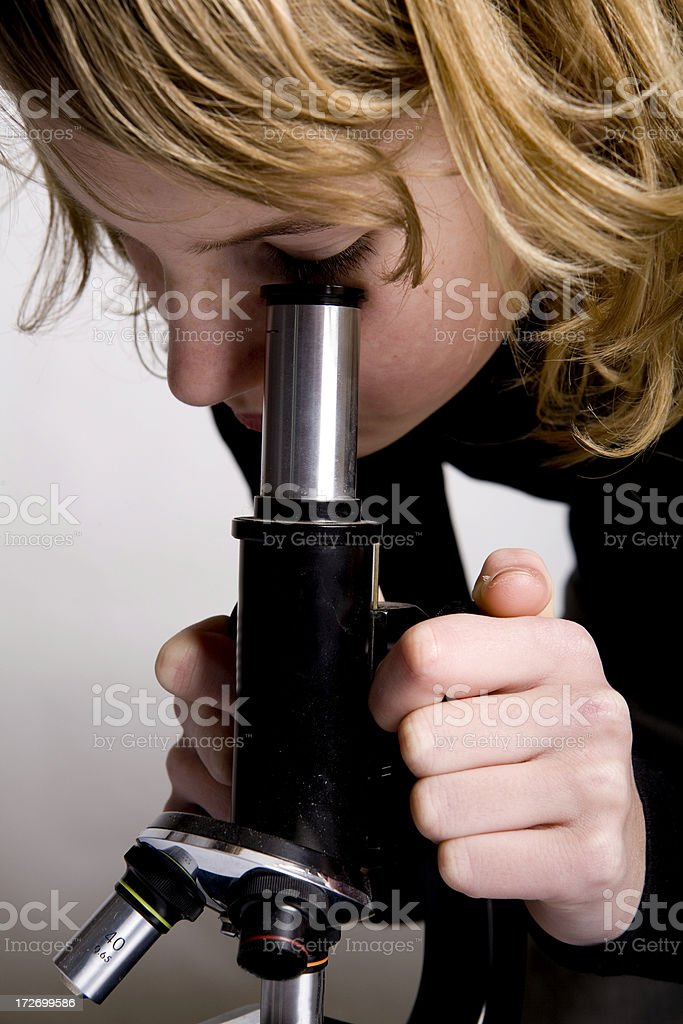 Girl looking through microscope researching royalty-free stock photo