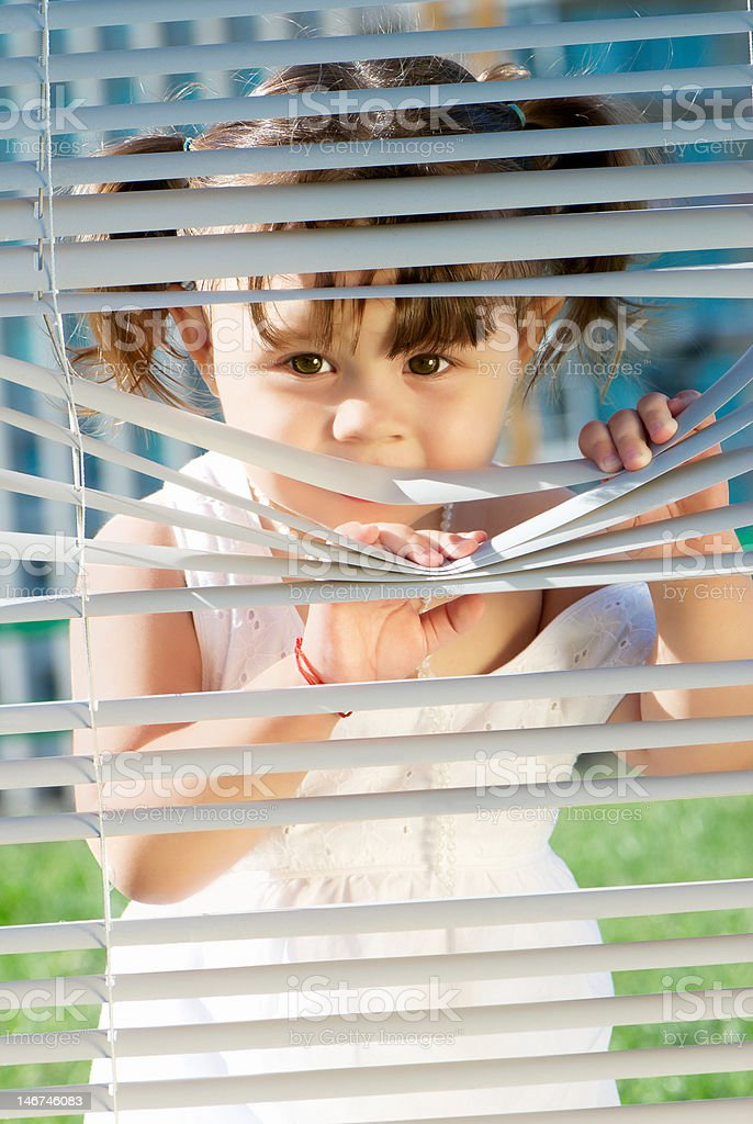 girl looking through the blinds royalty-free stock photo