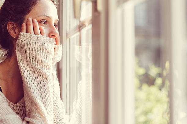 girl looking through the window - disappointment stock pictures, royalty-free photos & images