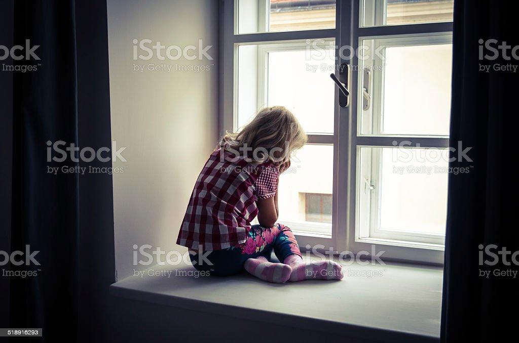 girl looking through window stock photo