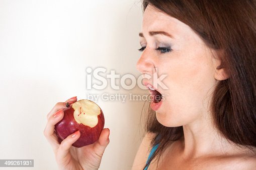 104545719istockphoto Girl looking to bloodshot apple 499261931
