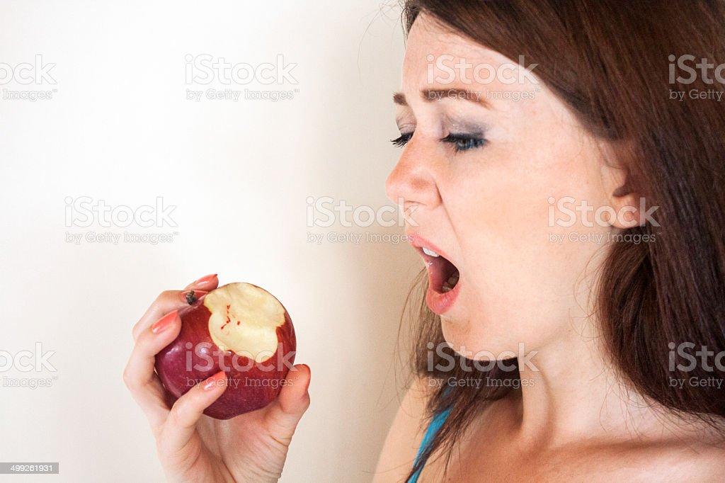 Girl looking to bloodshot apple stock photo