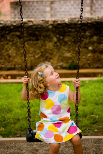 Colorful dressed Girl looking to the sky on a swing.