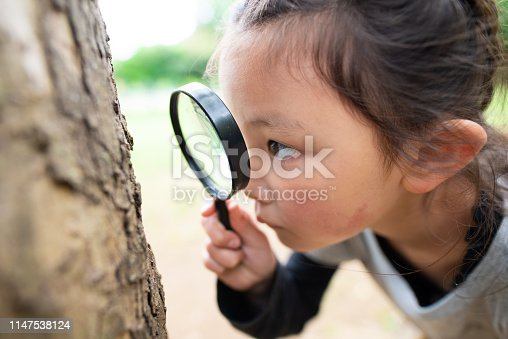istock Girl looking with magnifying glass 1147538124
