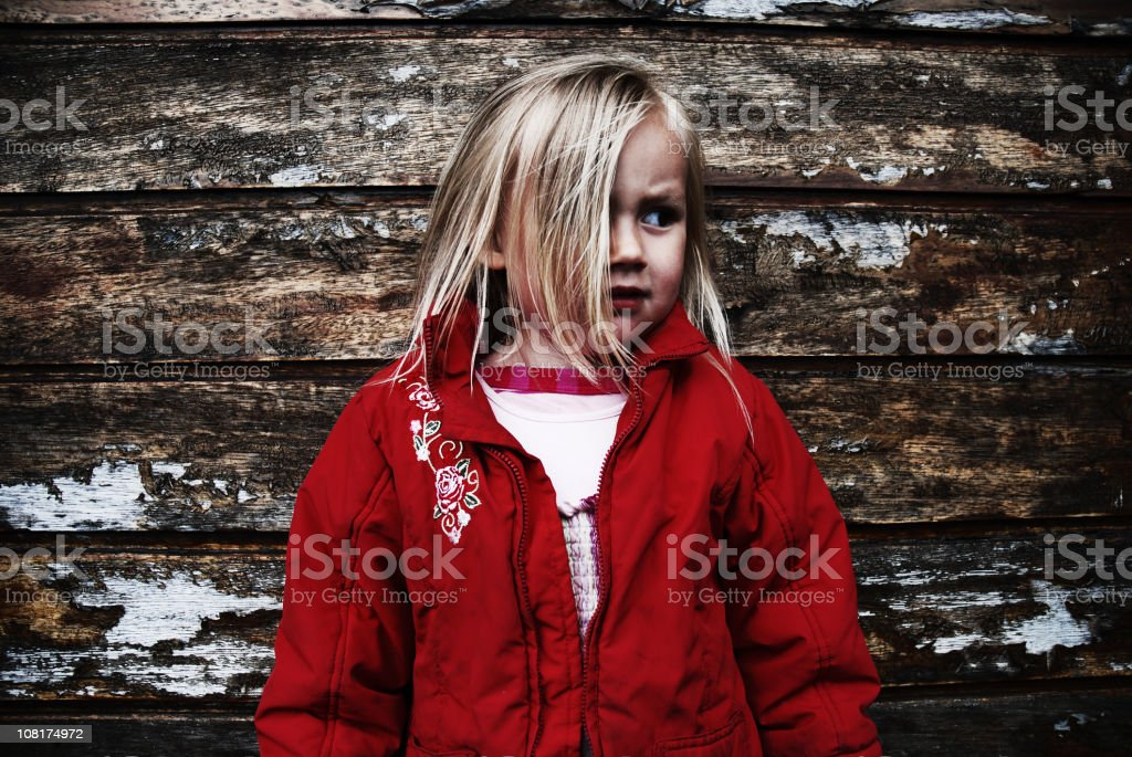 Girl looking worried standing in front of old wall royalty-free stock photo