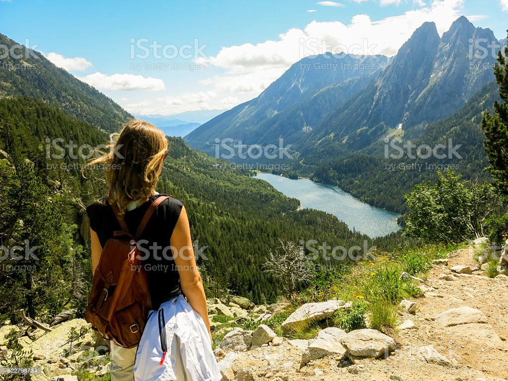 Girl looks at beautiful mountain view on a hike stock photo