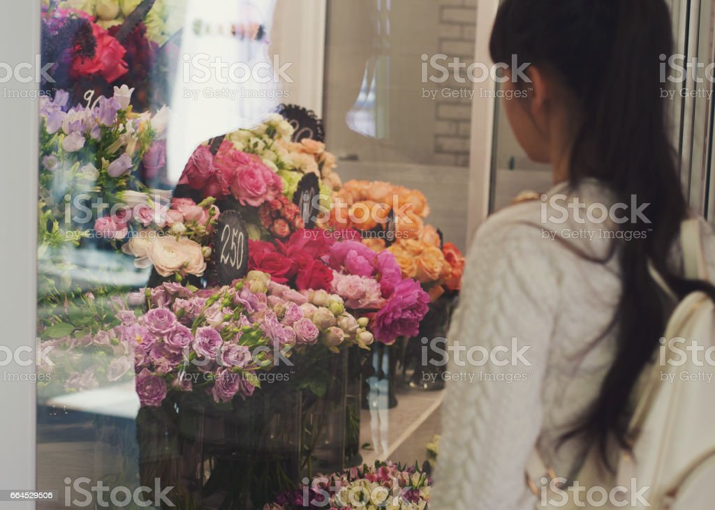 Girl looks at the flower shop window with different varieties of roses. royalty-free stock photo