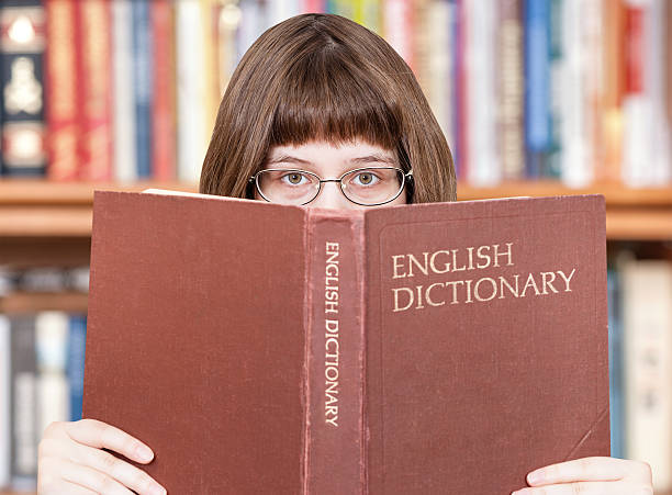 girl looks over English Dictionary and books stock photo