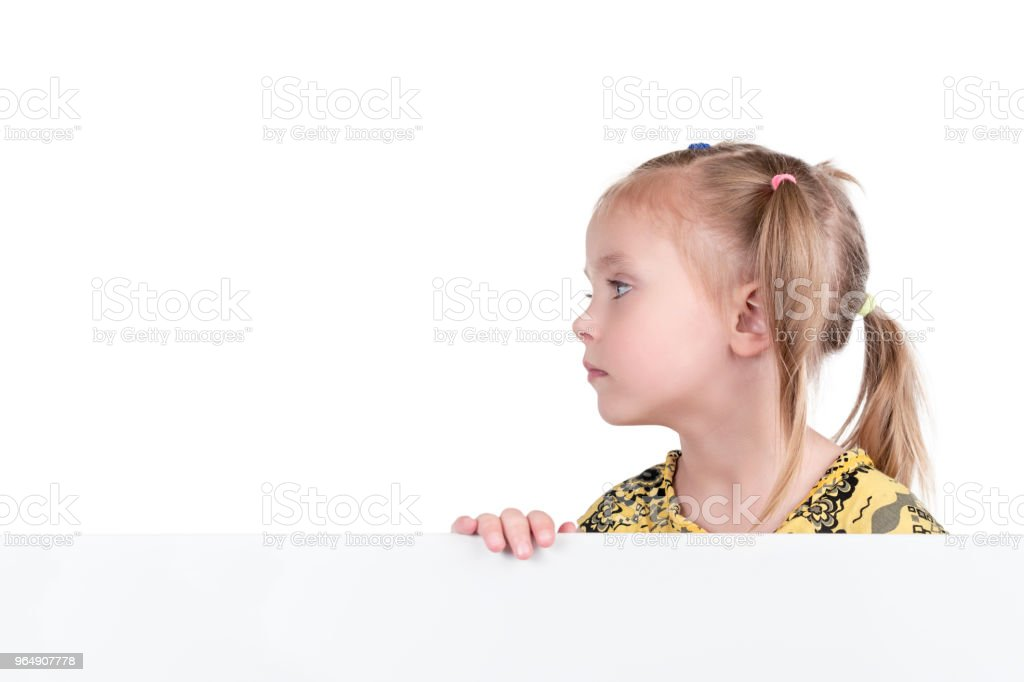 Girl looks sideways from behind the board royalty-free stock photo