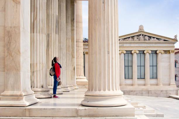 een meisje kijkt omhoog naar het plafond, in de kolommen van de atheense academie - geschiedenis stockfoto's en -beelden
