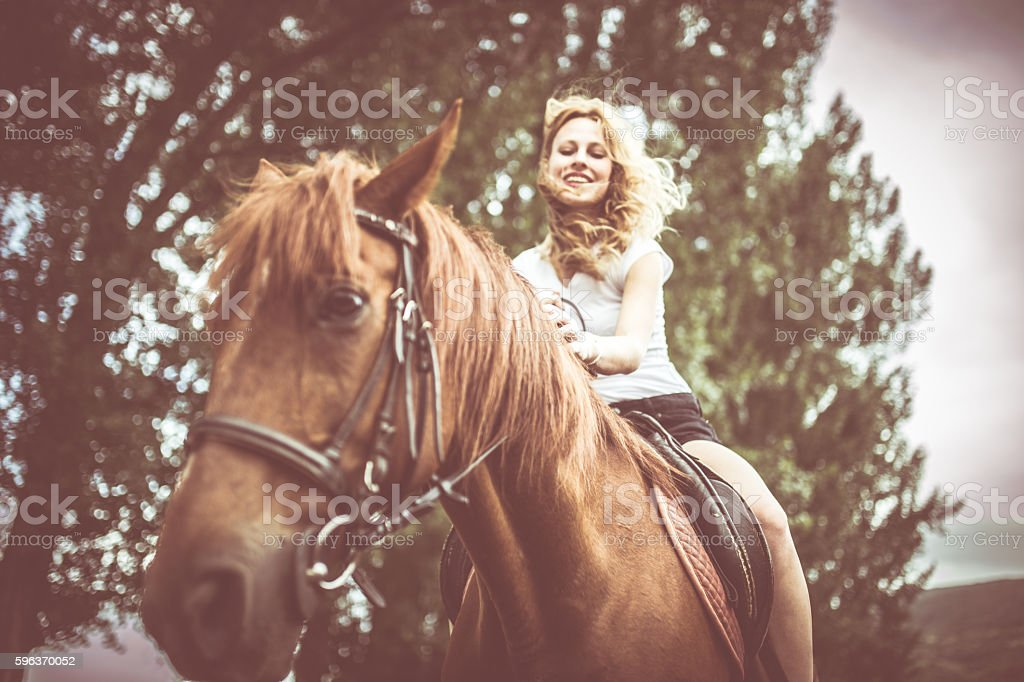 Beautiful blonde girl riding a brown horse on a ranch in summertime