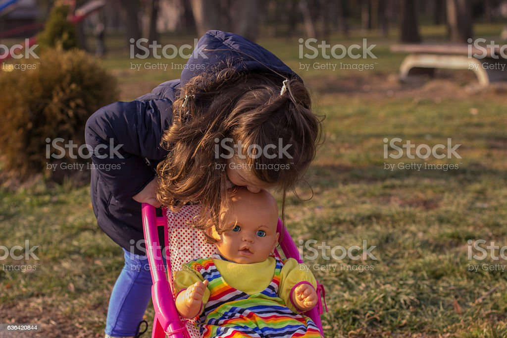 Girl pushing carriage doll on winter day