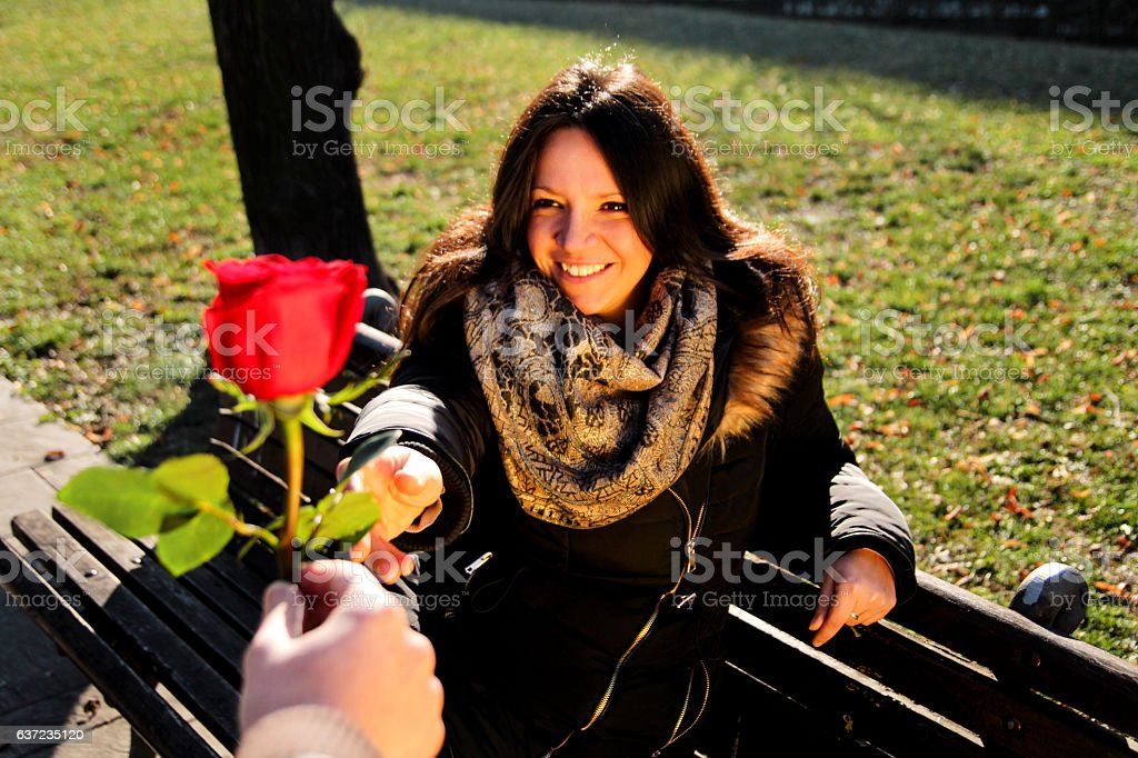 Girl lovingly looking at the hand and a red rose - foto de acervo