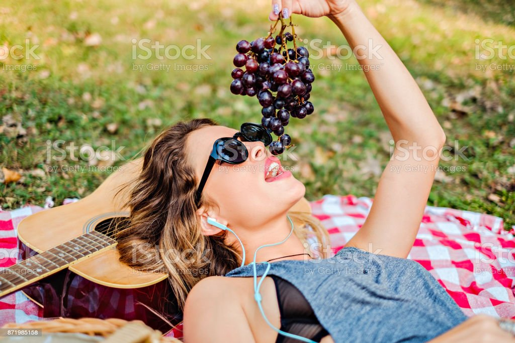 Girl lying and eating grapes in the park stock photo