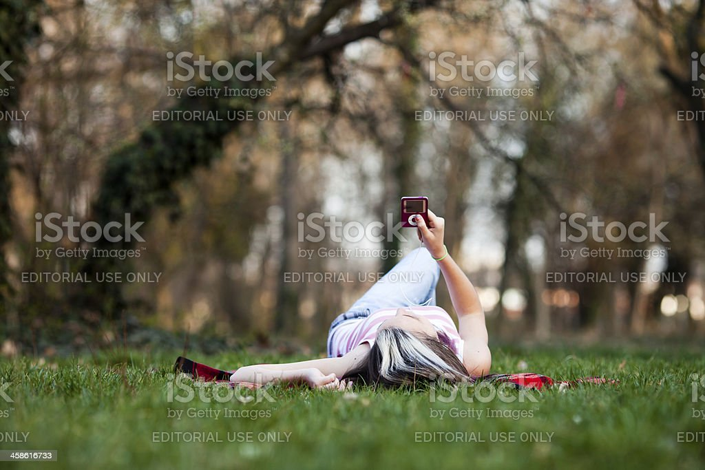 girl lying and listen to music on ipod stock photo