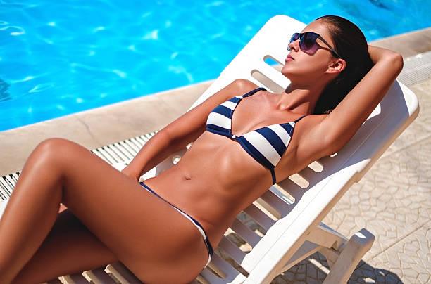 Girl lying and sunbathing by the pool - foto de stock
