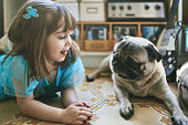 Cute girl looking at pug while lying on carpet. Kid is sticking out tongue while relaxing by dog. They are at home.