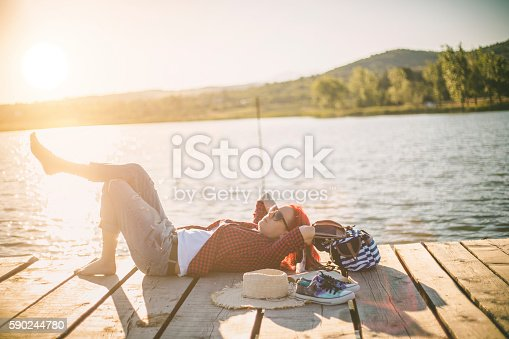 Beautiful girl resting on a wooden pier