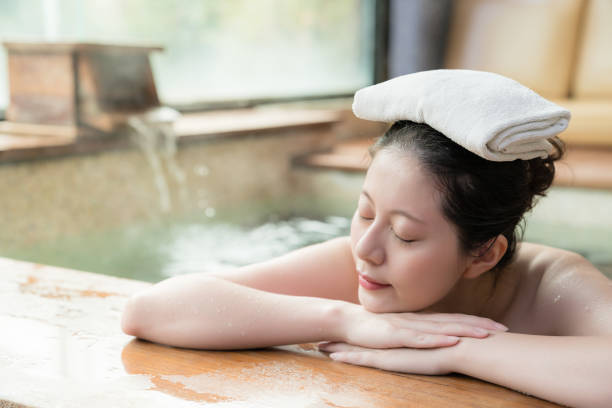 girl lying down on poolside and put a towel japanese girl lying down on poolside sleep and put a towel on her head while water flows on the background. hot spring stock pictures, royalty-free photos & images