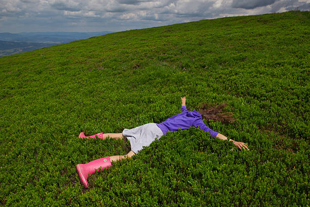 Girl lying facedown on the green bluberry field Girl lying facedown on the green bluberry field in the Carpatian mountain face down stock pictures, royalty-free photos & images