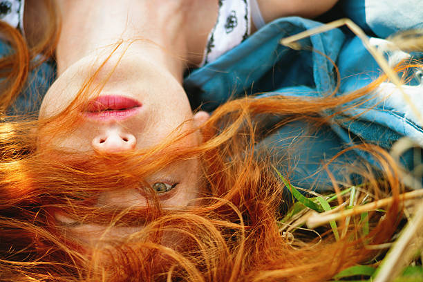 Girl lying in a meadow Redhead young girl lying in a meadow redhead stock pictures, royalty-free photos & images