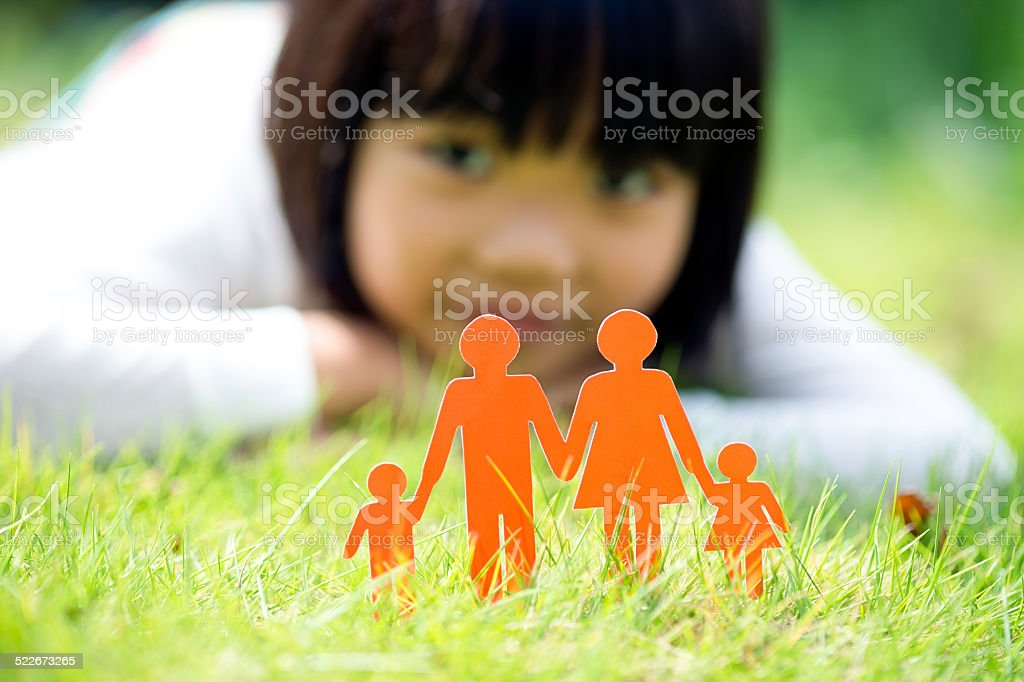 Girl Lying in Front of Family Paper Cut Out stock photo