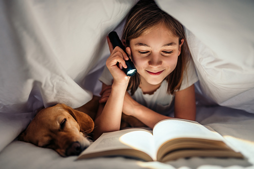 Girl lying in the bed with her dog under blanket reading book late at night