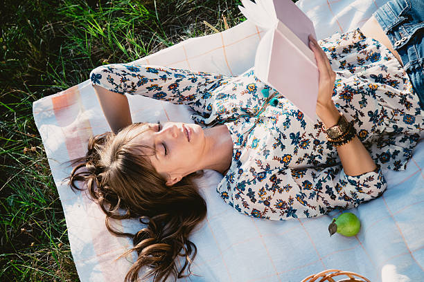 Chica de mentira en el parque y lectura - foto de stock
