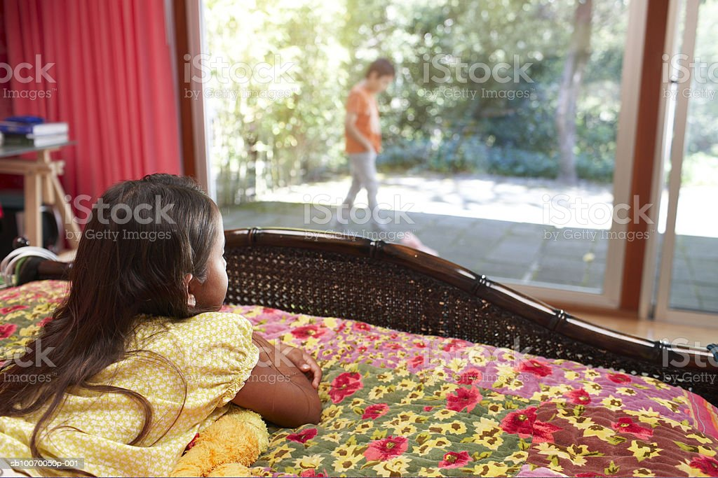 Girl (6-11) lying on bed and looking at boy through window royalty free stockfoto