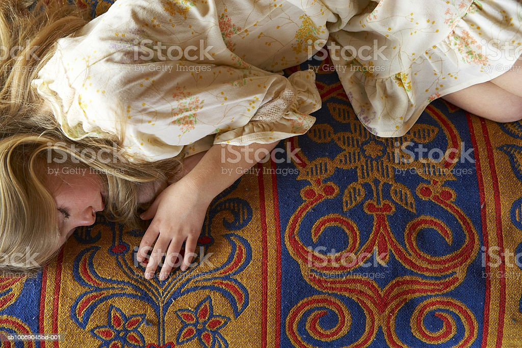 Girl (10-11) lying on bed, elevated view royalty-free stock photo