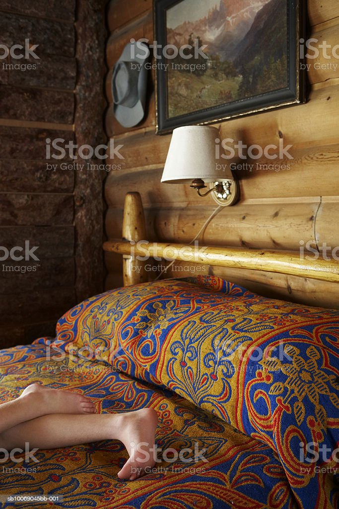 Girl (10-11) lying on bed, low section royalty-free stock photo
